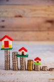 House models with stacked coins at wooden table business asset c Royalty Free Stock Photos