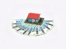 House with money. Over white background - mortgaging concept stock images