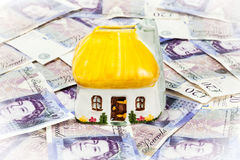House and Money. Money box house surrounded by cash notes. Light vignette used to add focal point effect Royalty Free Stock Photo