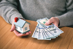 House and money. buy real estate, home mortgage. hands holding new hundred-dollar bills and toy house. Real estate agent Stock Photos