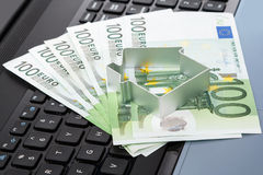 House and money  over laptop keyboard Stock Images