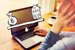 House and money on the scale with man using a laptop stock images