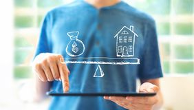 House and money on the scale with man using a tablet. House and money on the scale with young man using a tablet computer royalty free stock photography