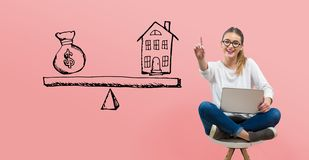 House and money on the scale with young woman. Using her laptop royalty free stock photos