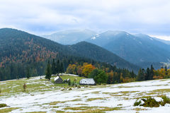 House Mountain alpine meadow on the background of mountain peaks and autumnal forest Royalty Free Stock Photo
