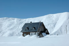 House in mountains. During winter stock image