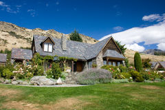 House in the mountains. Idyllic house on a slope of Southern Alps, Queenstown, New Zealand stock image