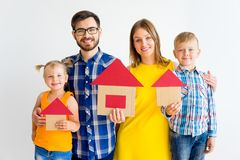 House move concept. Happy family holding cardboard home Stock Photo