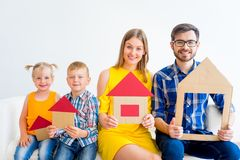 House move concept. Happy family holding cardboard home Stock Image