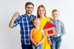 House move concept. Happy family holding cardboard home Stock Images