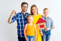 House move concept. Happy family holding cardboard home Royalty Free Stock Photography