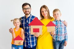 House move concept. Happy family holding cardboard home Royalty Free Stock Photos