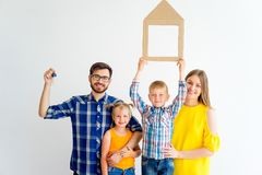 House move concept. Happy family holding cardboard home Royalty Free Stock Image