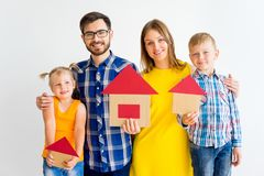 House move concept. Happy family holding cardboard home Stock Photos