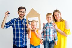 House move concept. Happy family holding cardboard home Royalty Free Stock Images