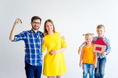 House move concept. Happy family holding cardboard home Royalty Free Stock Photo