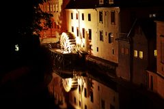 House with the moving of a wheel of a watermill. Beautiful art night view of the house with the moving of a wheel of a watermill with reflex of architecture of Stock Photo