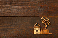House of my childhood. Beautiful creative design of house, fence and tree of the wooden parts in the children's style on brown table Stock Images