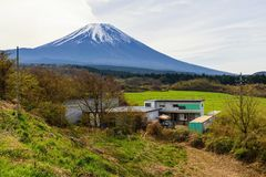 House in nature with mt. fuji view. House surrounding by  trees and farming near mountain fuji or Fujisan in spring, Yamanashi, Japan Royalty Free Stock Photo