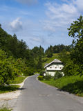 House near the bad country road. Cracked asphalt country road in Slovenia royalty free stock photo