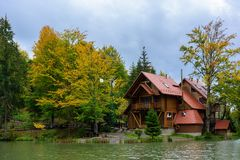 House near the lake in the forest, autumn day. Leaf fall landscape royalty free stock images