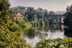 House near the river. House in green thickets of palm trees, on the bank of the small river, India Royalty Free Stock Images