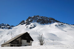 House near snowed peak in Pyrenees Royalty Free Stock Images