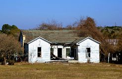 House in Need of Repair. Damaged house with roof caving in and missing windows could illustrate storm or fire damage remodeling insurance needs etc Stock Photos