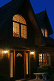 House at Night. A log crafted house with cedar shake roof against an evening sky Stock Image