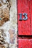 House number 13 on antique rustic wall, old, rusty metal numbers stock photography