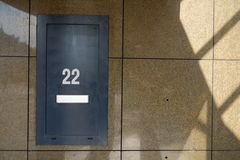 A house number on a building that says 22. A large building that has number 22. Underneath we see a mailbox Stock Photography
