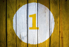 House number or calendar date in white circle on yellow toned wooden door background. Number one 1.  royalty free stock photography