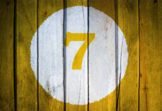 House number or calendar date in white circle on yellow toned wooden door background. Number seven 7 stock image