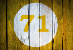 House number or calendar date in white circle on yellow toned wo Royalty Free Stock Image