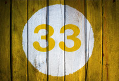 House number or calendar date in white circle on yellow toned wooden door background. Number thirty three 33 royalty free stock photography