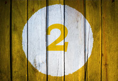 House number or calendar date in white circle on yellow toned wooden door background. Number two 2.  royalty free stock image