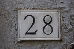 House number 28. House door number 28 in the wall Stock Photo