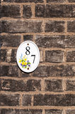 House number eighty seven mounted on a brick wall Royalty Free Stock Photo