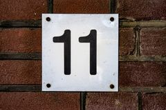 House number eleven 11. On a brick wall Royalty Free Stock Photos