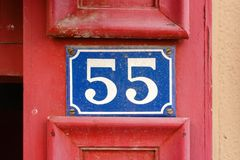 House number 55. Enameled house  number fifty five 55 on a red doorpost Stock Image