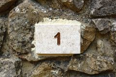 House Number 1 engraved in stone. House number one 1 engraved in stone, on a rough stone wall Stock Image