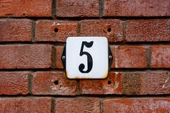 HOUSE NUMBER FIVE 5. On a red brick wall Royalty Free Stock Photography