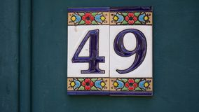 House number forty-ine 49 painted on ceramic tile in blue and yellow, red and gold from Israel royalty free stock photo