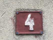 House number 4 on a grunge brown plate Stock Photo