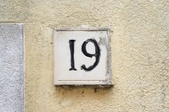 House number 19. House number nineteen 19 carved in stone and painted black, on a plastered wall Stock Images