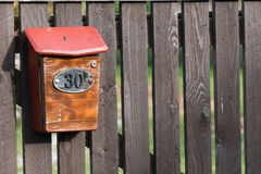 House number 30 on the mailbox on old wooden fence in a remote village stock photography