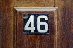 House number 46. Modern house number forty six 46 on a wooden door panel Royalty Free Stock Image