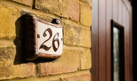 A house number next to a door. 26 stock photo
