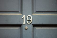 House number 19 with the nineteen in silver on a gray wooden door. Gray front door with a bronze or brass yellow number nineteen on it above a peep hole in the royalty free stock photos