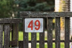 House number 49 on the old wooden fence in a remote village stock photo